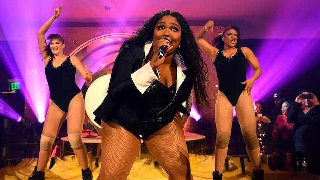 Lizzo chante sur scène en compagnie de danseuses.