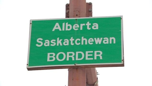 Une pancarte verte, avec des inscriptions blanches, accrochée à des feux de circulation.