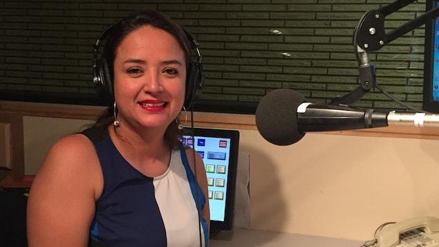 Johanna Silva Monroy au micro de «Le monde chez nous» à Vancouver. Elle porte une robe sans manches bleue et des boucles d'oreille.