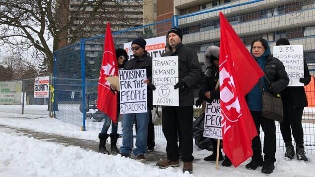 Une dizaine de personnes manifestent devant un immeuble avec des pancartes sur la neige.