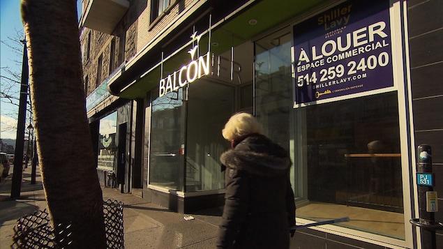 Une femme passe devant un local commercial vacant à Montréal.