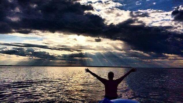 Une personne debout dans l'eau étend ses bras vers le soleil.
