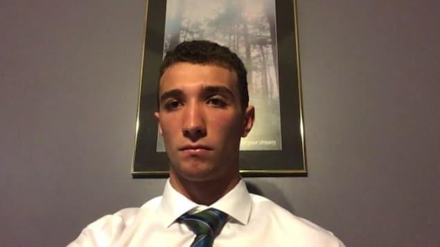 Il porte une chemise blanche et une cravate rayée.