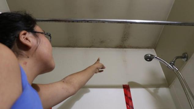 Une femme dans une salle de bain montre des moisissures sur le plafond et le mur
