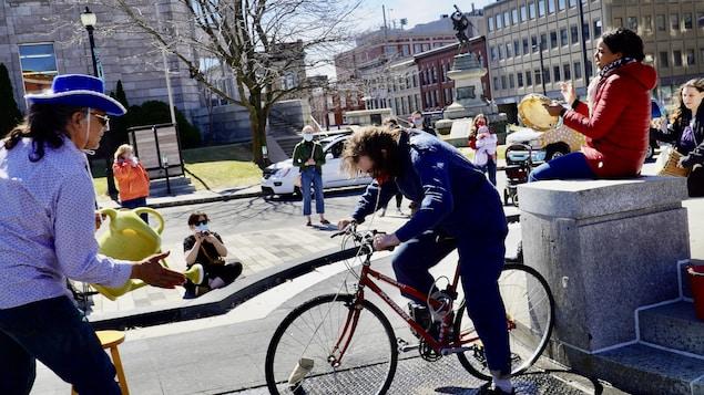 Des comédiens qui font une pièce de théâtre, dont un homme sur un vélo.