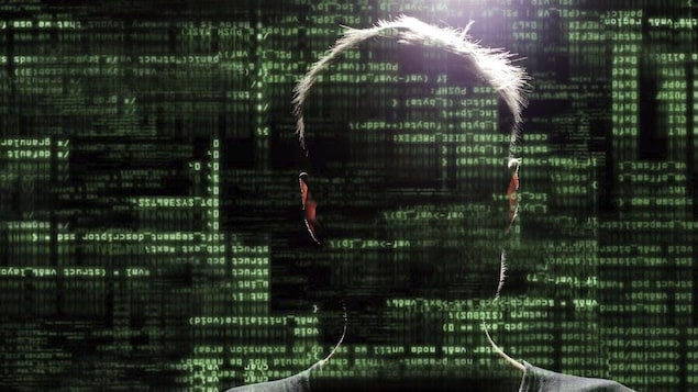 Un homme sans visage regarde un écran d'ordinateur.