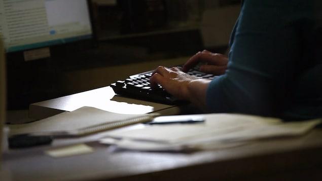 Une femme tape à l'ordinateur.