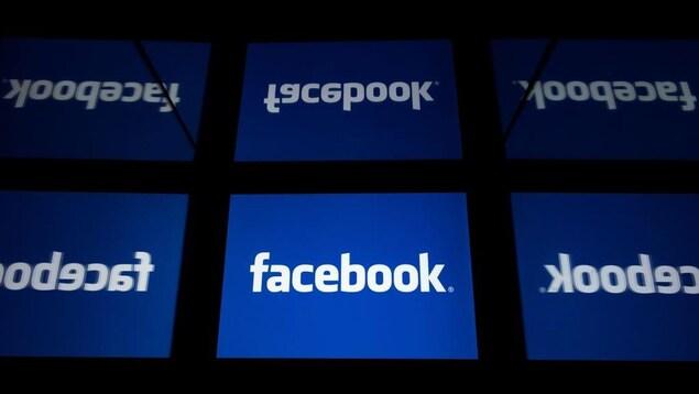 Des écrans arborent le logo blanc et bleu de Facebook