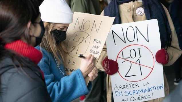 Des femmes tiennent des pancartes contre la loi 21.