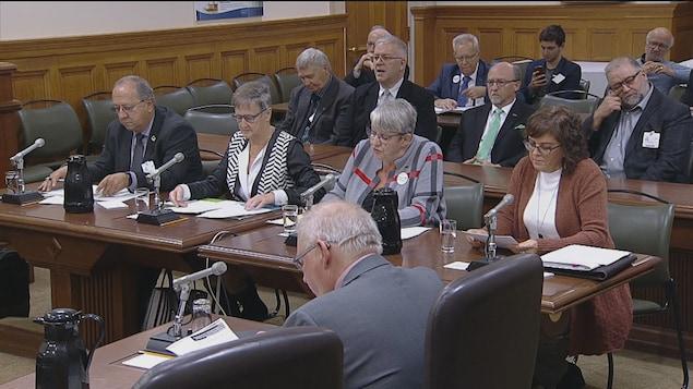 Quatre personnes assises à une table avec d'autres personnes derrière.