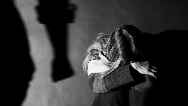Une femme assise se cache les yeux pour ne pas voir son partenaire violent.