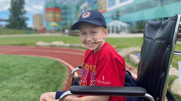 Loic Germaine dans un fauteuil roulant devant l'hôpital pour enfants de l'Alberta à Calgary.