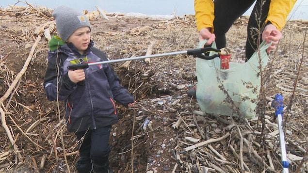 Un bambin ramasse des déchets sur une plage.