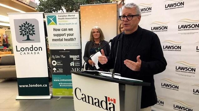 Un homme parle à un lutrin sur lequel il est inscrit Canada.