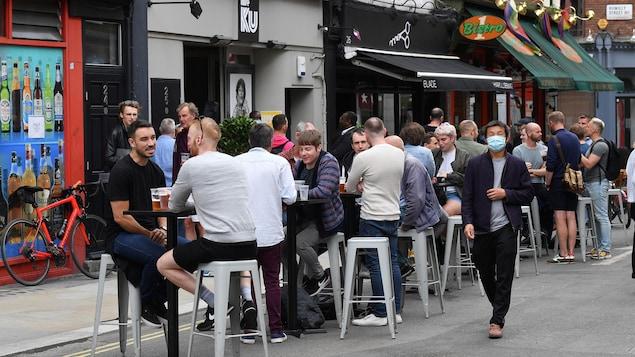 Des clients devant les bars rouverts de Soho à Londres le 4 juillet 2020.