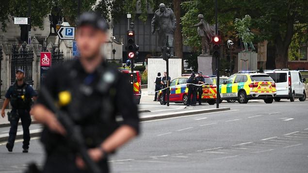 Un policier armé se tient à l'extérieur du palais de Westminster.