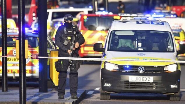 Un policier armé entouré de voitures de police.