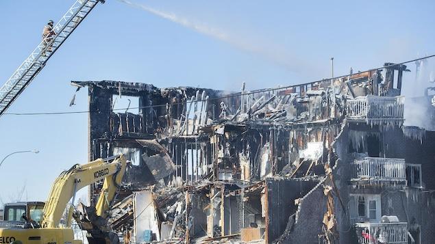 Une pelle mécanique travaille à démolir un bâtiment très gravement endommagé par les flammes.