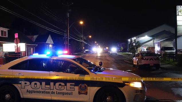 Une voiture de police est stationnée au travers de la route derrière un cordon de sécurité en pleine nuit.