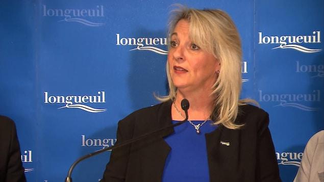La mairesse de Longueuil Sylvie Parent devant un panneau sur lequel figure le logo de la Ville.