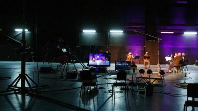 Dans un immense studio d'enregistrement vidéo sombre, les musiciens sont sous un éclairage coloré.
