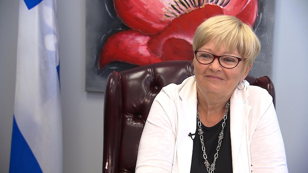 Lorraine Richard est assise dans son bureau. Elle est souriante.