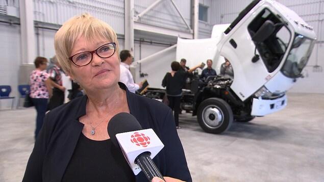 Lorraine Richard regarde au loin. À l'arrière, un camion-remorque a le capot ouvert.