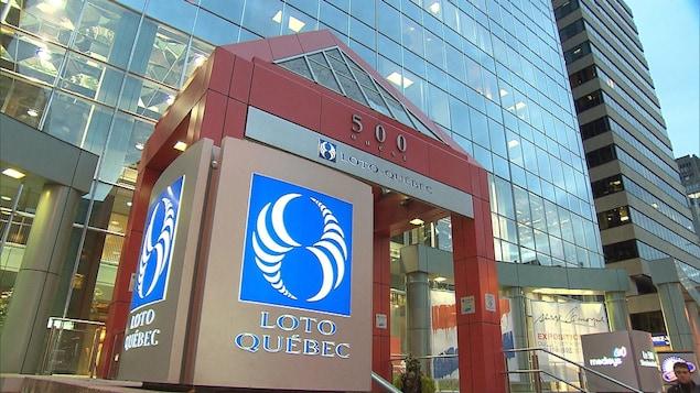 Un logo circulaire bleu et blanc, sous lequel on peut lire Loto Québec, est photographié devant un gratte-ciel.