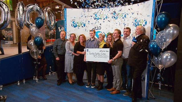 Les huit membres de la famille posent avec un chèque de 70 000 000 de dollars. Des confettis sont lancés dans les airs.