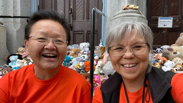 Residential school survivor Lou-ann Neel, right, with her sister Joani Glendale on the steps of a Catholic church in Victoria. Neel has found homes with primarily First Nations families for an estimated 200 stuffed animals and 100 pairs of children's shoes left at a vigil to honour the children who never came home from a residential school in Kamloops, B.C.