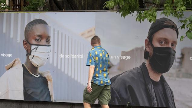 Un homme passe devant un panneau publicitaire sur lequel apparaissent Loud et Sarahmée portant un couvre-visage.