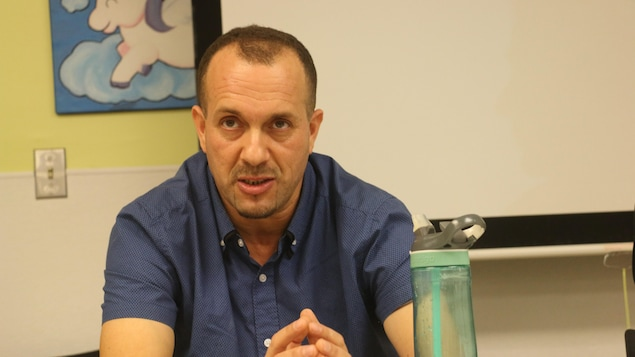 Portrait de l'auteur Louenas Hassani, assis, en chemisette bleue, avec une gourde en premier plan.