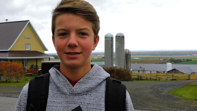 On voit l'adolescent de face, en gros plan, devant la ferme familiale à Saint-Michel-de-Bellechasse.