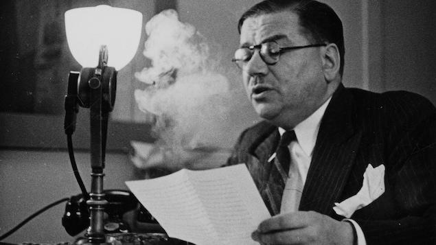 Dans un studio de radio, assis à un bureau, le journaliste Louis Francoeur parle au micro avec son texte dans la main. Une épaisse volute de fumée de sa cigarette monte au-dessus de la feuille.