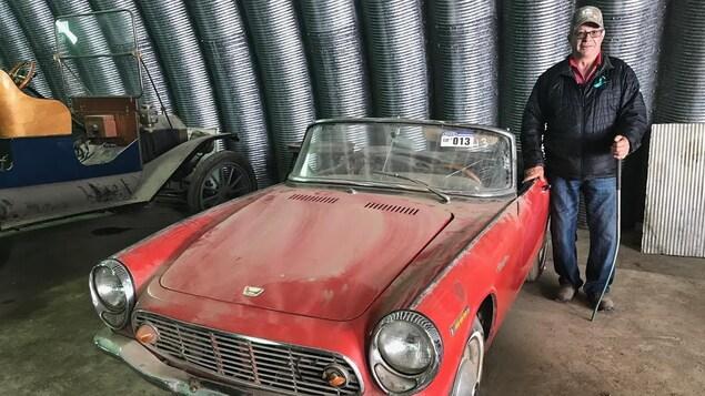 Un homme souriant est debout à côté d'une voiture rouge décapotable