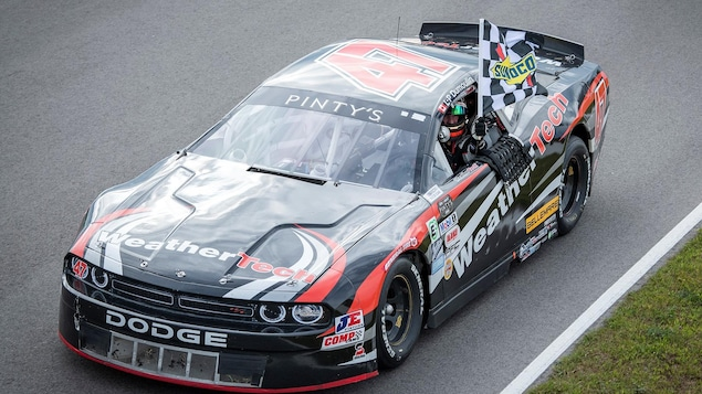 Louis-Philippe Dumoulin au volant de sa voiture de Nascar Pinty's, un drapeau à damiers à la main.