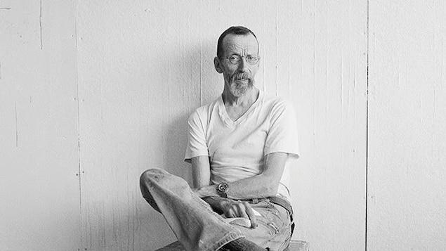 L'homme vêtu d'un t-shirt blanc est assis sur un tabouret, les jambes croisées, devant un mur blanc.
