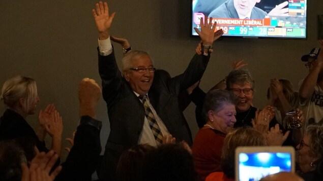 Louis Plamondon les bras dans les airs entouré de militants.