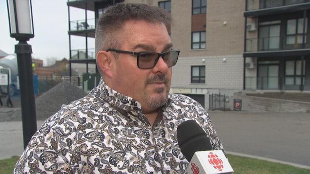 Louis Sauvé en entrevue à Radio-Canada devant un immeuble à logements.