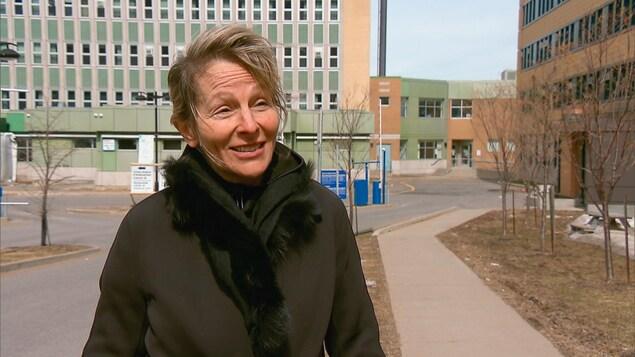 La médecin Louise Caron devant l'hôpital Jeffery Hale à Québec, elle porte un manteau noir. Elle est souriante.