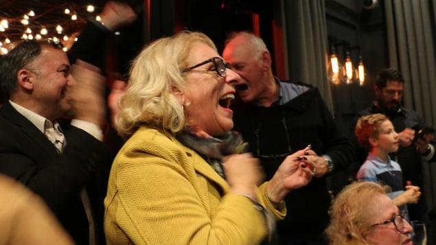 La candidate et ses militants heureux autour dans une salle.