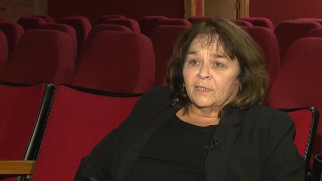 Louise Lalonde donne un entrevue dans une salle de projection.