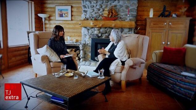 Julie Larouche et Louise Portal assises sur des fauteuils devant un foyer