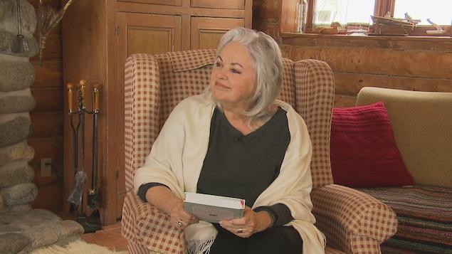 Louise Portal est assise dans un fauteuil et elle tient un livre.