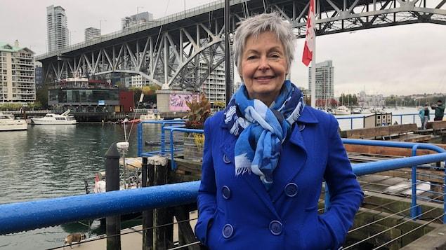 Louise Turgeon sourit près d'une balustrade au bord de l'eau.