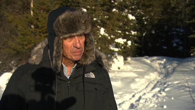 Luc Deschênes accorde une entrevue à Radio-Canada dans un boisé près du noyau urbain.