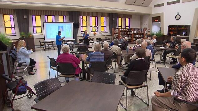 Plusieurs aînés suivent une formation dans une salle commune dans la résidence Saint-Eugène.