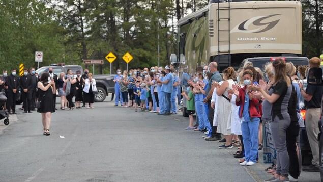 Une cinquantaine de personnes portent un masque et applaudissent dans la rue.