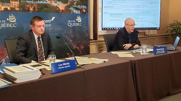 Luc Monty et Daniel Genest sont assis sur une table lors d'une conférence, devant un écran. Ils parlent devant un micro.