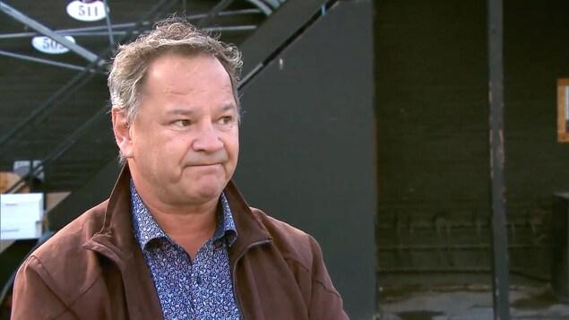 Le propriétaire du bar Kirouac, Lucien Simard, à l'extérieur en entrevue. Il porte un manteau brun